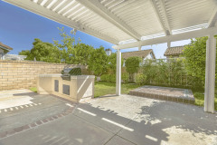 Concrete Patio Of A Home With Barbecue Grill And White Wooden Pergola