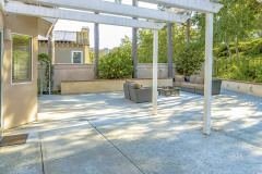 Panorama Frame Patio With A White Wooden Pergola Attached To The Wall Of The Home