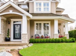 The front entry area of a suburban home with a well-trimmed yard and furnished porch area