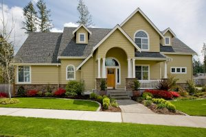 The exterior od a suburban home with a well-kept front yard, porch, and curve-top windows